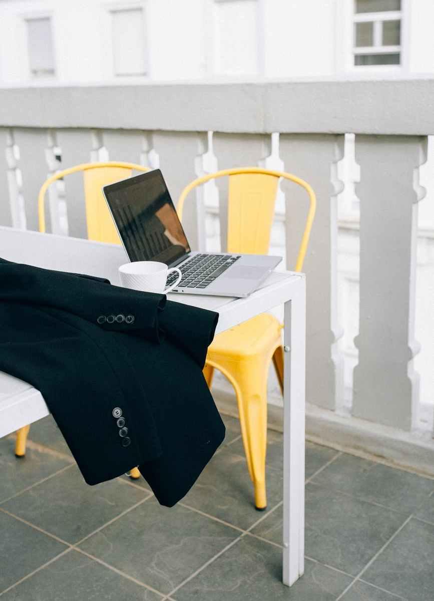 black laptop computer on white plastic armchair