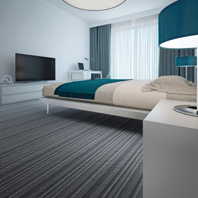 Lindisfarne herringbone tufted carpet installed in a modern, minimalist hotel room.