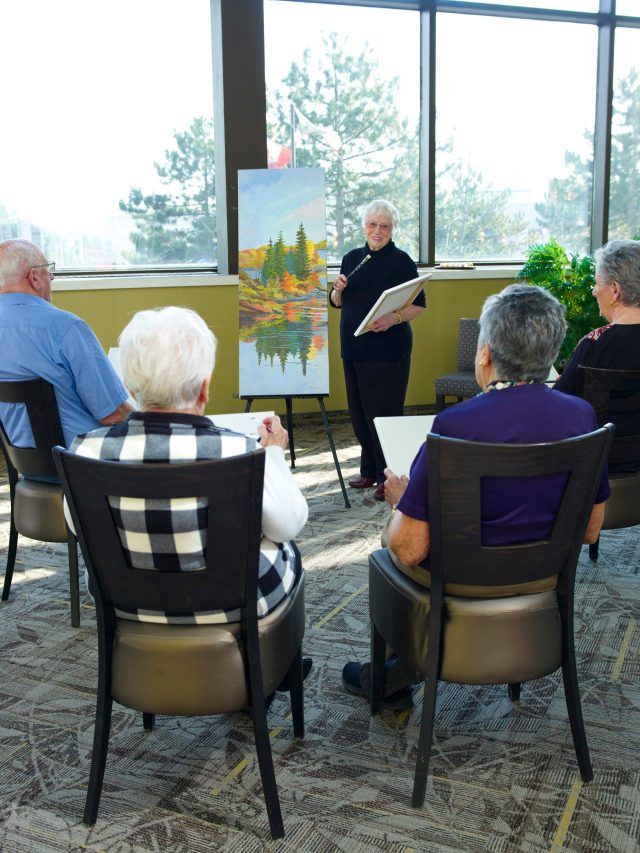 Group of seniors taking part in a painting class, part of the activities and recreation program at Winchester Glen Retirement Community.