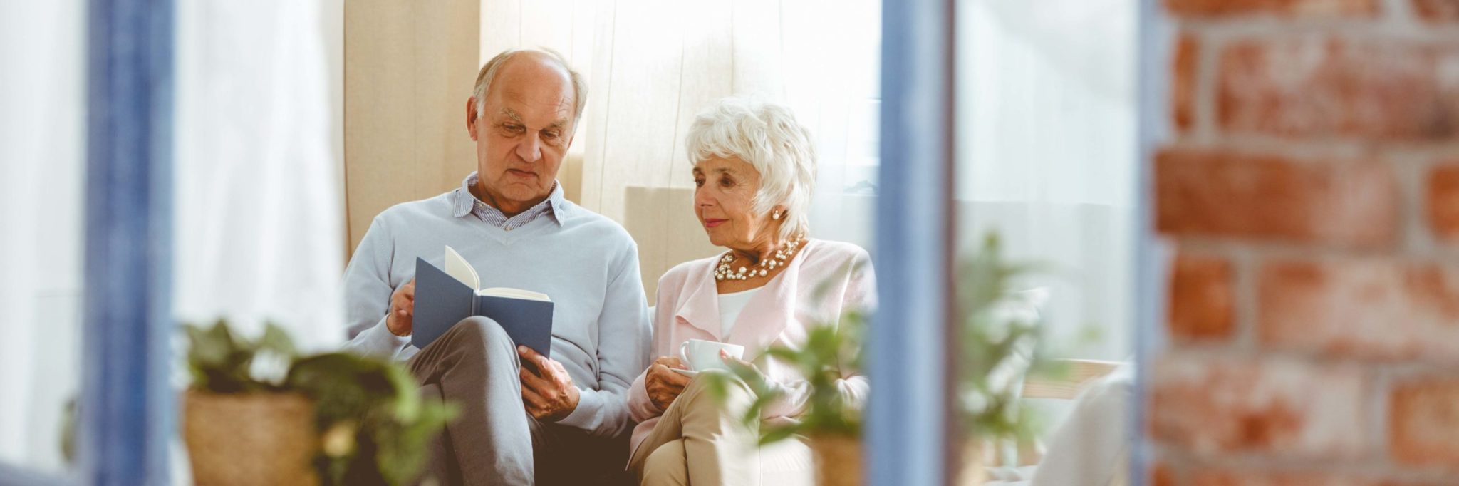 Elderly couple sitting together and reviewing the floorplans of the spacious private suites offered at Winchester Glen Retirement Community.