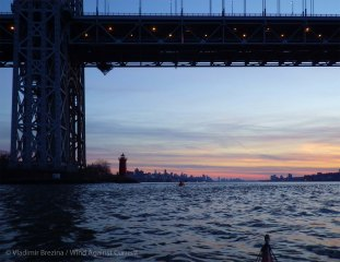 Under the George Washington Bridge, the Manhattan skyline comes once more into view