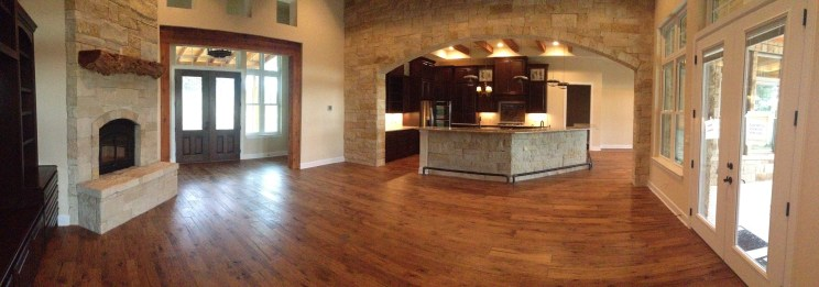 The open plan living area and kitchen feature hardwood floors and natural stone throughout.
