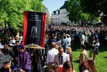 Graduates, faculty and staff recess out from the commencement ceremony through the Daniel Pavilion.