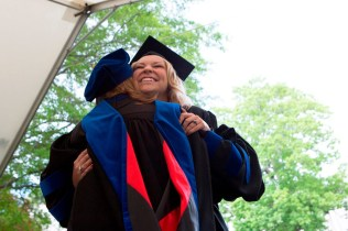 Brenau University's Katie Barth of Duluth, Georgia, hugs Debra Dobkins, dean of Brenau's Women's College, as she goes to get her diploma during this year's Women's College Commencement.