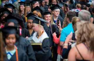 Women's College graduates recess from commencement services through the Daniel Pavilion.