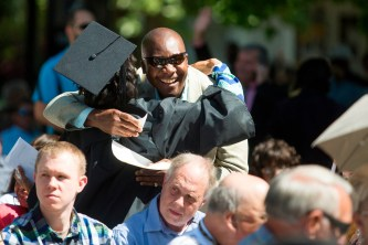 Robert Vil hugs his daughter Cassandra Carmel Vil-WIlson during this year's Women's College commencement ceremony.