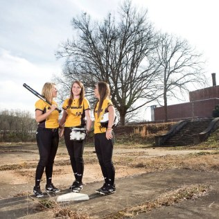 Brenau softball players, from left, Cheyenne Marsh, Jenny Shepherd and Mackenzie Oliver stand on the future site of the Brenau University Athletic Complex next to the Milliken plant in Gainesville, Ga.