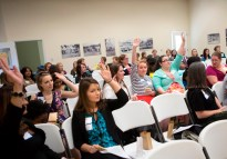 Brenau University students, faculty and staff, and Gainesville community members raise their hands to share the most creative thing a cardboard box could be used for during Lee Anne Romberg White's portion of the Women's Leadership Colloquium.