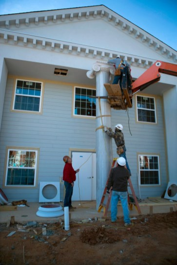 Crews from Caroll Daniel Construction raise a column on the second of four new sorority houses built along Prior Street.