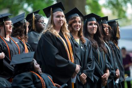 Brenau Women stand as they have their degrees conferred upon them by Brenau University President Ed Schrader.