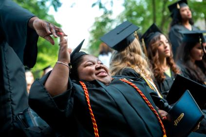 Byronica Banks, the student government association president, high fives her friend Staricka Cummings during the 2015 Women's College Commencement