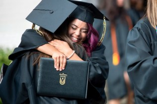 Amanda Bonilla hugs her friend Samantha Miles after receiving her Bachelor of Fine Arts degree.