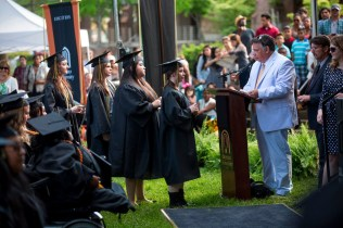 Jay Andrews, director of broadcasting and digital communications at Brenau, reads names as the 2015 Women's College graduates walk up to the stage.