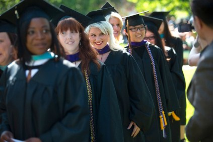 Amanda Dunahoo smiles to the crowd as she walks up to the stage to receive her Master of Interior Design degree during the 2015 Undergraduate and Graduate Commencement at Brenau.