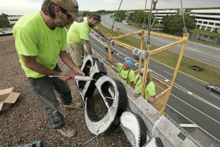 Workers from General Sign Service install the sign for Brenau University on the office building at 6622 Southpoint Drive South, home to the school's new Jacksonville, Florida, campus Wednesday, June 10, 2015. (Bob Self/For Brenau University)