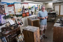 Dennis Campay stands in his Jacksonville, Florida, studio among a mural and art supplies.