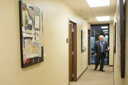 Brenau CFO David Barnett tours the Jacksonville campus, with walls adorned with the artwork of Dennis Campay.