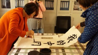 """The principal of one school we visited demonstrates how to paint Chinese calligraphy. This beautiful example, which says """"Your China Dream,"""" is now on the wall of my office here at home."""