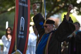 Stewart Blakley celebrates as his retirement is mentioned as he accepts the Vulcan Teaching Award during The Women's College commencement on Friday, May 6, 2016, in Gainesville, Ga. (AJ Reynolds/Brenau University)