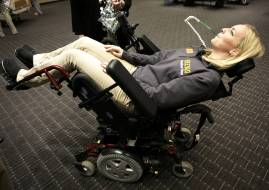 "Brenau University occupational therapy graduate student Lauren Tomy discovers how lean back a ""Sip & Puff Power Wheelchair"" by blowing on a straw. (Phil Skinner for Brenau University)"