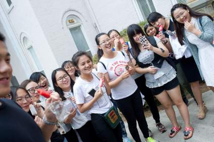 From left to right, Harry Deng, Jocelyn Heng, Belle Ni, Cherry Hong, Becky Xu, Rachel Pei, Lisa Wang, Miao Miao Yu, Amy Yang, Daisy Qiu, Lavender Qin, Sarah Morales, Cathy Wu and Lily Li react as Brenau President Ed Schrader's chocolate lab Jake jumps to greet Vice President of Communications David Morrison, not pictured. (AJ Reynolds/Brenau University)