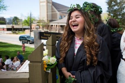 Nancy Benitez, a graduating senior, waits to pass her robe to a junior. (AJ Reynolds/Brenau University)