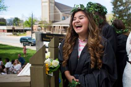 Nancy Benitez, a graduating senior, waits to pass her robe to a junior. (AJ Reynolds/Brenau University)