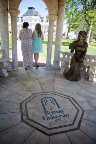 Sophomore Hannah Adams is escorted from the Daniel Pavillon by her mother Gina during the procession of the May Court. (AJ Reynolds/Brenau University)