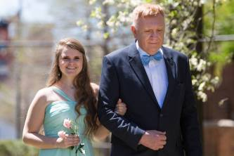 Megan Bullins, left, is escorted by her grandfather, Phillip Iddings as they process from the Daniel Pavilion to take her place on the May Court. (AJ Reynolds/Brenau University)