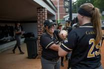 Brenau's Kelsey Payne, center, and Jessica Rathje laugh inside the team's dugout. (AJ Reynolds/Brenau University)
