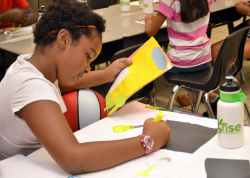 """Aalliyah Glasper works on a story she wrote titled """"Arizona"""" and a poster to accompany it during the RISE Summer Program."""