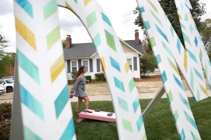 Kailey Posea plays corn hole with a fellow sorority sister shown through the Phi Mu sorority letters in front of the Phi Mu house during the sorority open house of the Alumnae Reunion Weekend & May Day at Brenau University Saturday, April 14, 2018, in Gainesville, Ga. Photo by Jason Getz / Brenau University