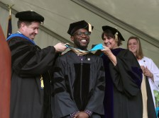 Brenau University Provost James Eck, left, and Chair of the Physical Therapy Department Kathye Light fixes the academic regalia of Marcus Belizaire as he receives his doctorate in physical therapy during the graduate and undergraduate commencement Saturday May 5, 2018 in Gainesville, Ga. (Jason Getz for Brenau University)