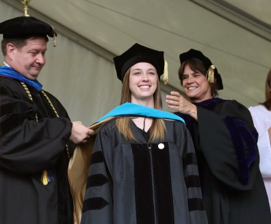 Brenau University Provost James Eck, left, and Chair of the Physical Therapy Department Kathye Light fixes the academic regalia of Hannah Evans as she receives her doctorate in physical therapy during the graduate and undergraduate commencement Saturday May 5, 2018 in Gainesville, Ga. (Jason Getz for Brenau University)