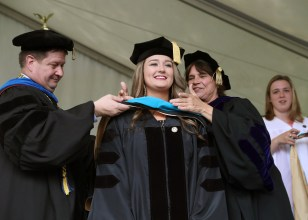 Brenau University Provost James Eck, left, and Chair of the Physical Therapy Department Kathye Light fixes the academic regalia of Rey Holcomb-Payne as she receives her doctorate in physical therapy during the graduate and undergraduate commencement Saturday May 5, 2018 in Gainesville, Ga. (Jason Getz for Brenau University)