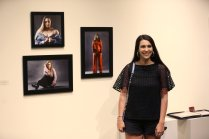 Fallin Britt gets a photograph of herself with her work at an art show during the Brenau Collaborative art show during Alumnae Reunion Weekend & May Day at Brenau University Saturday, April 14, 2018, in Gainesville, Ga. Photo by Jason Getz / Brenau University