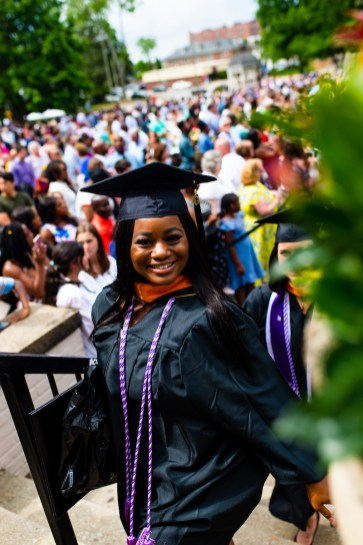 Woman in regalia walks up steps smiling at commencement