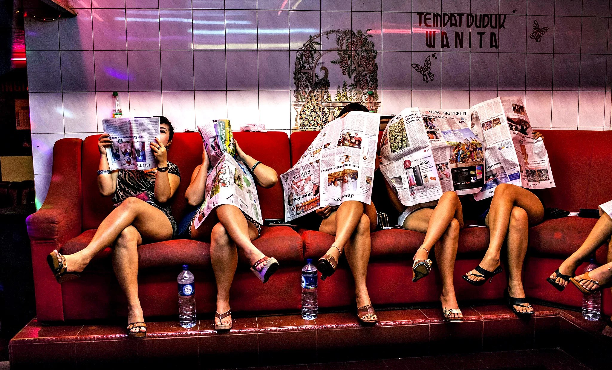 """""""Dolly"""" Brothel Remains Open Despite Closure Of Red-Light District...SURABAYA, INDONESIA - JUNE 20: Indonesian commercial female sex workers cover their face sit lined up behind the glass inside a brothel as the activity still runs after being closed by Surabaya's new Mayor at 'Dolly' red-light district on June 20, 2014 in Surabaya, Indonesia. Despite protests by some local residents and sex-workers, Surabaya's new Mayor, Tri Rismaharini closed the 'Dolly' and neighbouring 'Jarak' red-light district in Surabaya, Indonesia's second-largest city, on Wednesday. Many of the community support the end of sex trade in Dolly's streets, with some Islamic groups reportedly threatening violence should the brothels not remain closed. (Photo by Ulet Ifansasti/Getty Images)"""