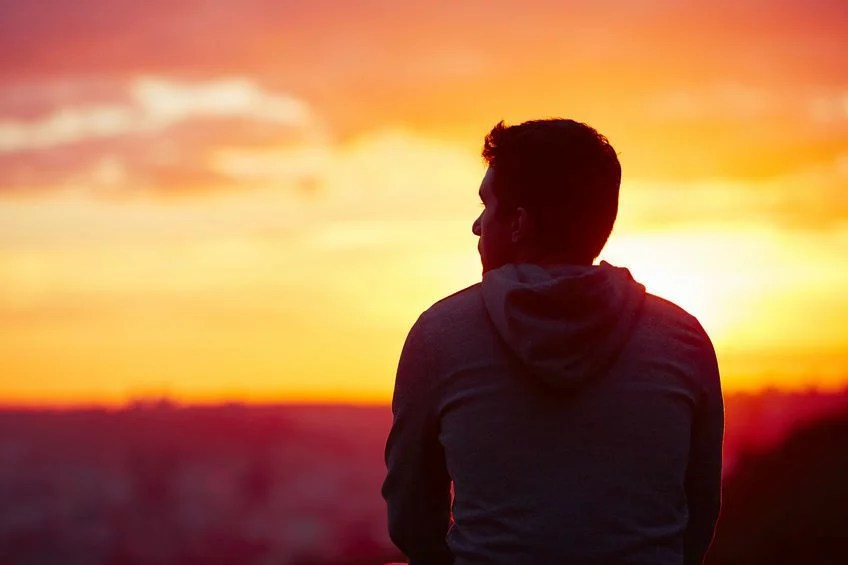 45778974 - young man is looking at the sunrise.