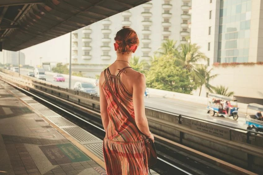 36077705 - a young woman is standing on a train platform
