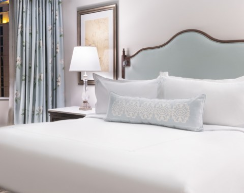 A premium suite at Windsor Court Hotel, featuring a king size bed, night stand with lamp, and nighttime view of New Orleans