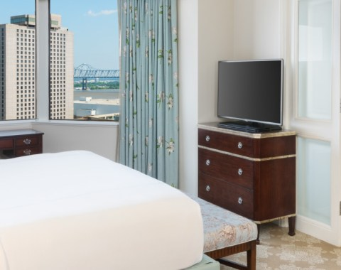 A premium suite at Windsor Court Hotel, featuring a king size bed, dresser with tv, and a window with a view of New Orleans