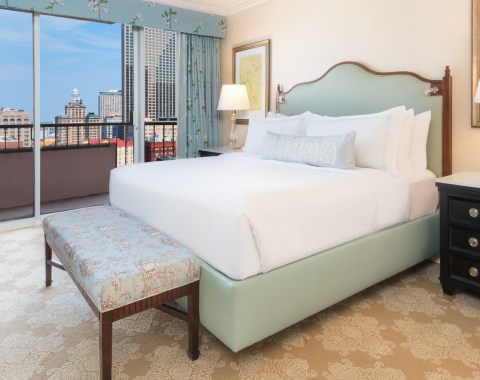 Deluxe Suite at Windsor Court Hotel, with a king size bed, tv and view of the New Orleans skyline from the private balcony