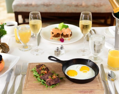 An array of in-room dining options including steak, eggs, fruit, orange juice, and champagne
