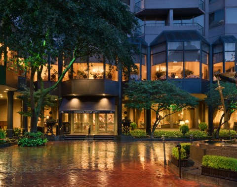 Exterior view of the Windsor Court Hotel and driveway at night