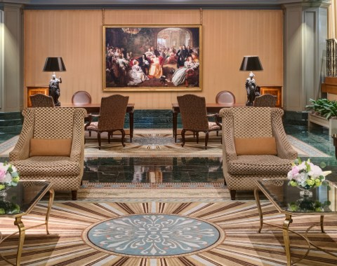 The lobby of the Windsor Court Hotel, furnished with brown tables and chairs and classic paintings