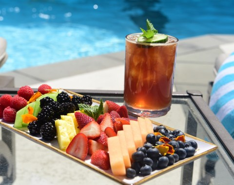 fruit tray featuring berries, melon and pineapple with Pimms Cup cocktail at rooftop poolside bar