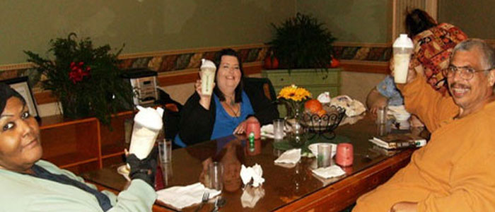 Bariatric patients swap stories over protein shakes in the dinning hall.