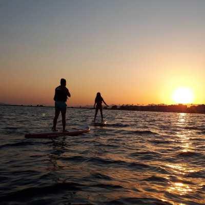 Dos personas realizando una excursión de paddle surf en el atardecer de Santa Pola