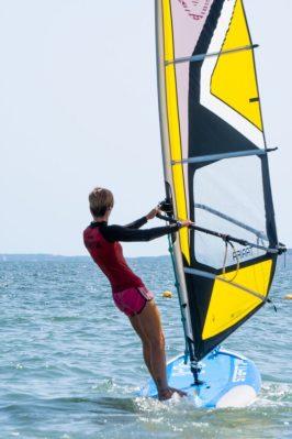 Mujer navegando en windsurf en el mar en verano